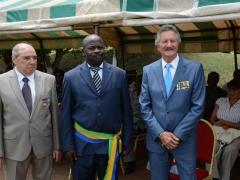 J.Pierre Fourès, Président des sections de l'étranger de l'Ordre National du Mérite et Pierre Grosjean, Président de la section Gabonaise, entourant le Maire de Cocobeach.